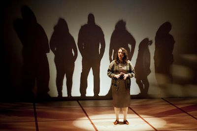Melanie Hampton as Lynn Reiner with all of the murder victims seen in silhouette behind a screen at the end of the play when Lynn tells how each of them died.